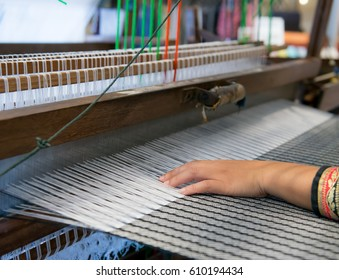 Weaving cloth for using in local village ,Woman working at the loom. Thailand national crafts. Focus on the fabric, classic asian loom at work, traditional thai loom detail, Weaving