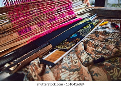 Weaving fabric. Weaving and manufacturing of handmade carpets closeup. Hand made on a wooden loom manufacture of thread and fabric