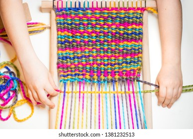 Weaving. Hands of little caucasian girl working on small loom weaving. Close-up photo isolated on white background.