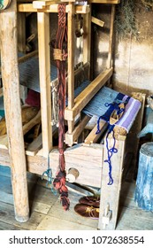Weaving loom and shuttle on the warp, Old loom with a shuttle, a tool designed to store a holder that carries the thread of the weft. Old hand loom during the weaving of the fabric, medieval age.