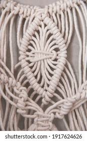 weaving macrame from cotton threads of white color against the background of a concrete wall