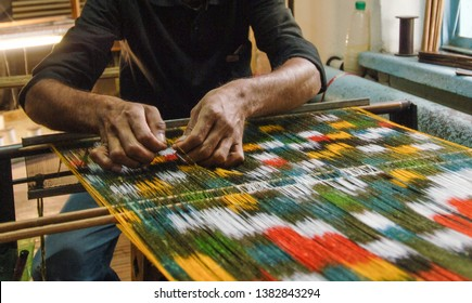 weaving and manufacturing of handmade carpets close-up. man's hands behind a loom