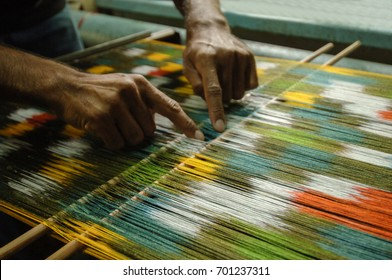 weaving and manufacturing of handmade carpets closeup. man's hands behind a loom