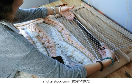 Weaving on a loom. Closeup woman's hands running on a loom. Threading the shuttle through the strands of frame and fasten the yarn with scallop.