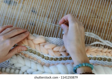 Weaving on a loom. Weaving on a loom. Closeup woman's hands running on a loom. Threading the needle through the strands of frame.