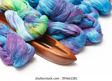 Weaving shuttle with colored yarns for needlework isolated on white