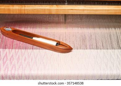 Weaving shuttle on the beige shade warp