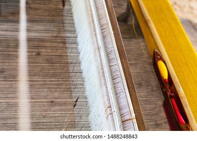 Weaving shuttle on weave silk cotton on the manual wood loom.