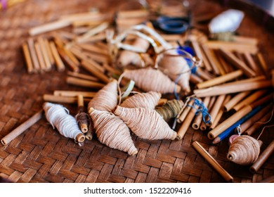 Weaving tool on woven bamboo. Old spool made by wooden. Cotton spool on woven bamboo