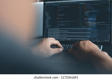 Web or application development, business and technology concept. Programmer, man software developer hands coding HTML, programming Javascript on laptop computer screen, back view close up