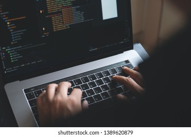 Web or application development, business and technology concept. Programmer, man software developer hands coding HTML, programming Javascript on laptop computer screen, over shoulder view close up