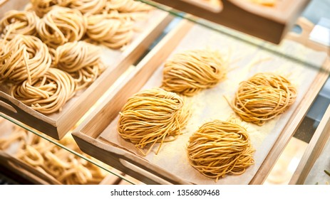 Web Banner 16 in 9 crop of Fettuccine nests. Various mix of uncooked pasta in the shop window. Different kind of dry macaroni in round form. Italian foods concept of spaghetti and menu design