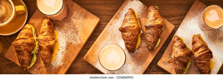 Web Banner 3 in 1 crop for design. Fresh croissant and original authors coffee with fruits on wooden table. Healthy breakfast food concept. Traditional french lunch in cafe with gold sunlight flare.