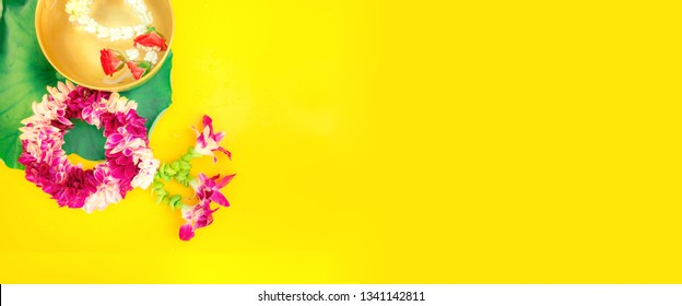 web banner design for spring and summer season festival concept from minimal flat lay tropical flower with orchid ,rose decorate on pastel yellow background for songkran ceremony of thailand)