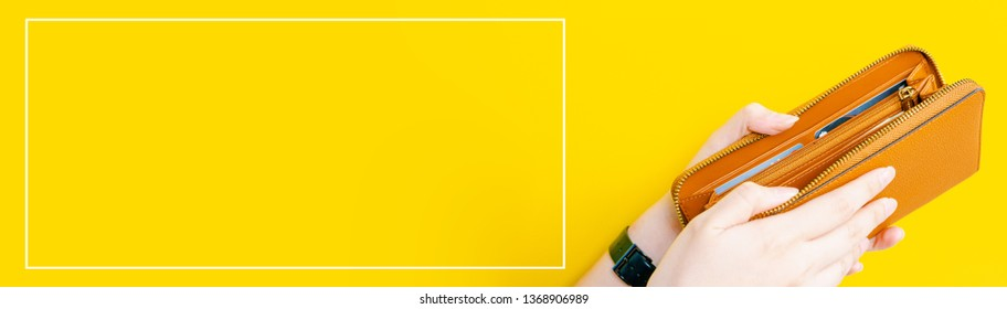 web banner design for woman fashion in spring and summer concept with beauty woman hand hold and open modern brown leather purse or wallet in left hand with yellow pastel background