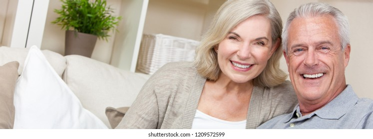 Web banner panoramic image of happy senior man and woman couple sitting together at home smiling and happy with perfect teeth
