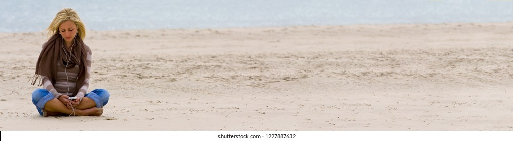 Web banner panoramic photograph of beautiful sad depressed young blond woman or girl sitting alone on a beach listening to music on headphones and smart phone