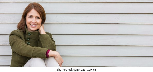 Web banner panoramic portrait shot of an attractive, single, successful and happy middle aged woman female smiling sitting down outside