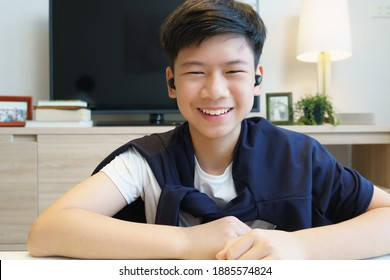 Web cam video call picture of a handsome young asian teenager boy's face with earbuds happy talking to distance friend through online chat application during Covid-19 pandemic lockdown. New normal.