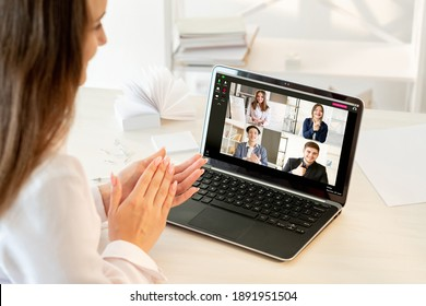 Web conference. Online presentation. Virtual meeting. Pandemic WFH. Cheerful diverse multiracial team supporting idea applauding to colleague on laptop screen at light modern home office workplace.