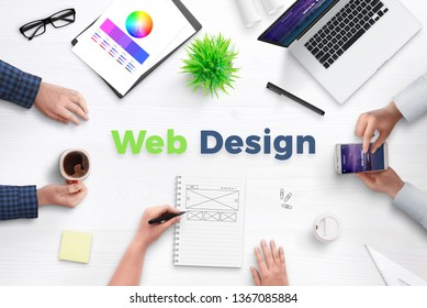 Web design text on work desk surrounded with web development team, devices, projects, and ideas on paper. Concept of team meeting.