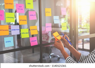 Web designer brainstorming for a strategy plan. Colorful sticky notes with things to do on office board. User experience (UX) concept.