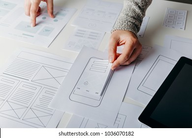Web designer creating mobile responsive website. Website wireframe sketches on white table