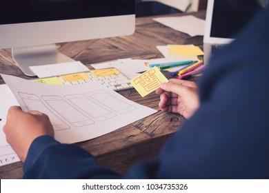 Web designer planning application for mobile phone. Design Online Technology Content, Ideas Proposal Strategy Tactics Vision Design Concept