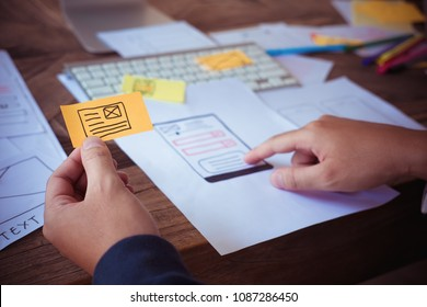 Web designer planning application for mobile phone. Design Online Technology Content, Ideas Proposal Strategy Tactics Vision Design Concept