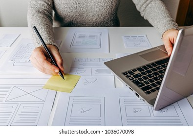 Web designer working at laptop and website wireframe sketches on white table