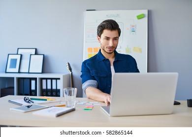 Web designer working on laptop in office
