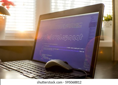 Web development phrase ASCII art inside HTML code. Web developer workplace in sunset lights. Abstract information technology background. Laptop and mouse on keyboard.