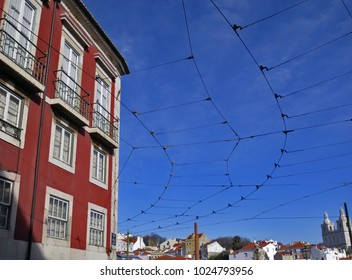 Web of tram cables with sky and clouds in background