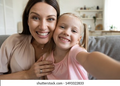 Webcam close up view pretty cheerful faces of little preschool daughter and young beautiful mother, kid girl holding camera family vloggers shooting recording new vlog feels happy enjoy funny activity