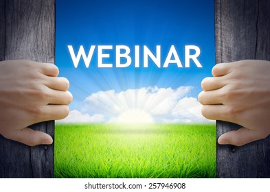 Webinar. Hand opening an old wooden door and found Webinar word floating over green field and bright blue Sky Sunrise.