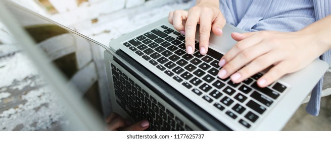 Website banner of closeup female hands typing on laptop keyboard. Concept of modern technology, blog heading and copywriter occupation.