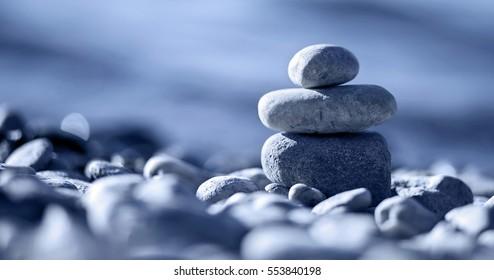 Website banner of Zen balancing pebbles on the beach in blue