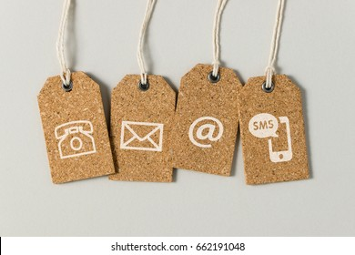 Website contact us icons on brown tags over grey background