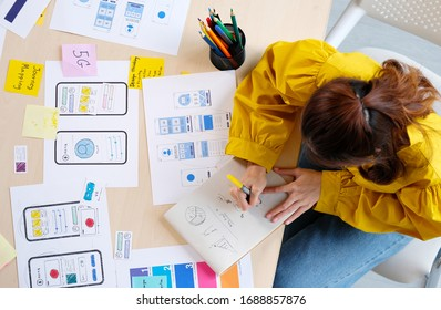 Website designer, Creative planning phone app development sketch template layout framework wireframe design, User experience concept, Overhead view of young woman UX designer web structure at home