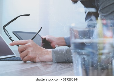 Website designer holding eyeglass working computer laptop,digital tablet on wood table screen graphic virtual icons,graph,diagram
