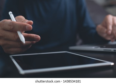 Website designer with stylus pen working digital tablet and computer laptop on wooden desk. Casual business man hand touching on touchpad screen, close up. Freelance online working from home, close up