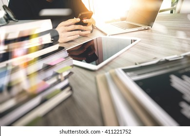 Website designer working digital tablet and computer laptop with smart phone and digital design diagram and stack of books on wooden desk as concept