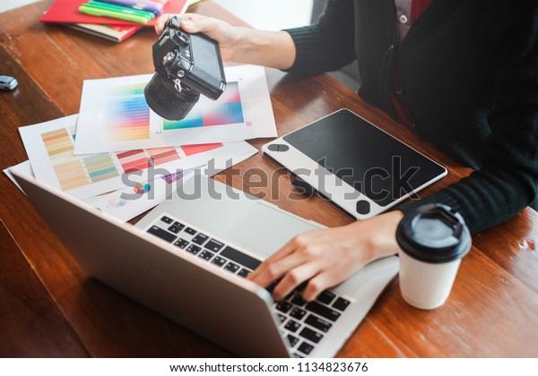 Website designer working digital tablet and computer laptop with smart phone and graphics design diagram in cafe.