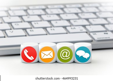Website and Internet contact us page concept with colored icons on cubes in front of a keyboard