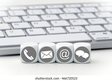 Website and Internet contact us page concept with white icons on cubes in front of a keyboard