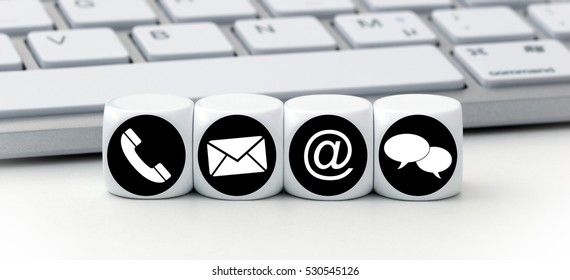 Website and Internet contact us page concept with black and white icons on cubes in front of a keyboard
