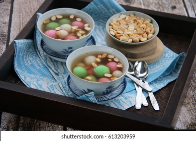 Wedang Ronde. Peranakan dessert of glutinous rice balls in warm ginger soup. Served in vintage china crockery on a rustic wooden table, with extra peanuts on side.