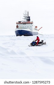 Weddell Sea, Antarctica – September 19, 2013: A scientist from the research icebreaker Polarstern is travelling to an ice camp by a snow mobile  over an ice floe.