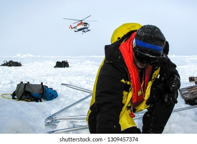 Weddell Sea, Antarctica – September 8, 2013: Scientist waiting for the landing of a helicopter during evacuation of a polar research camp over an ice floe due to cracking of the ice by storm swells.