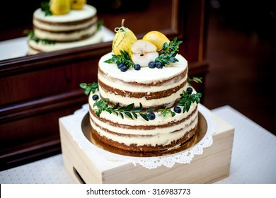 Wedding 2-tiered rustic nude cake with cream cheese and green leaves decor. Pear on top. Natural light.